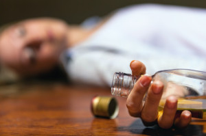 Drunken young woman lying on the floor. Focus on the bottle